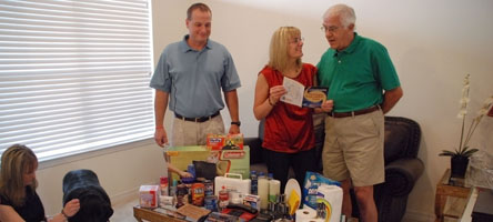 Graphic showing a family standing around a table full of products for a disaster supply kit